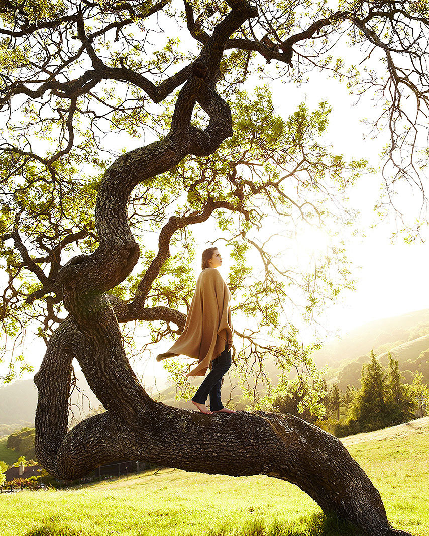 Side view of a teenage girl in thoughts on tree trunk
