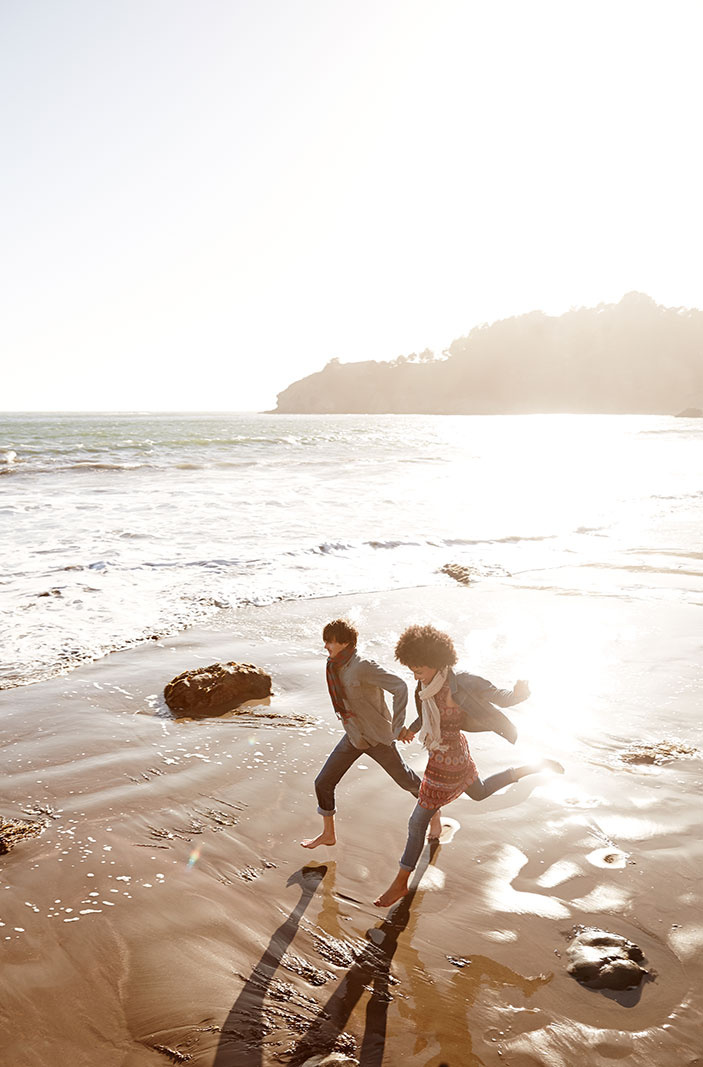 Young couple running on beach in CA  | Trinette+Chris Photographers