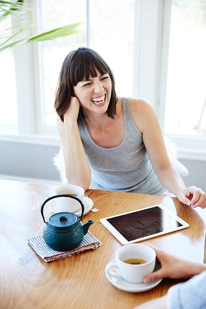 Woman laughing with ipad  | Trinette+Chris Photographers